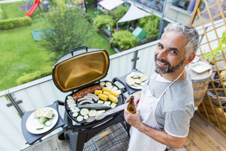 Smiling man barbecuing on his balcony model released Symbolfoto property released PUBLICATIONxINxGER